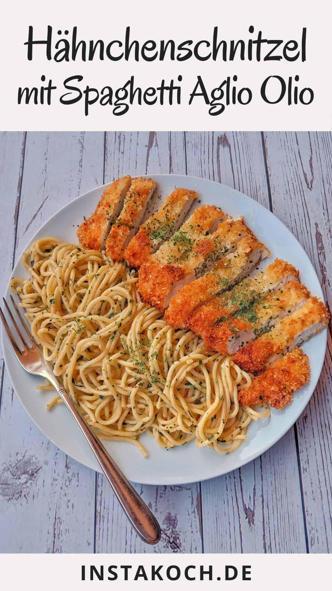Ein weisser Teller mit Spaghetti Aglio e Olio und einem Hähnchenschnitzel.