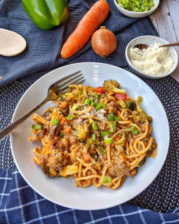 Ein weisser Teller mit der One pot pasta mit Brokkoli Champignons und Hackfleisch. Im Hintergrund ein Schälchen Parmesan und Gemüse als Deko.