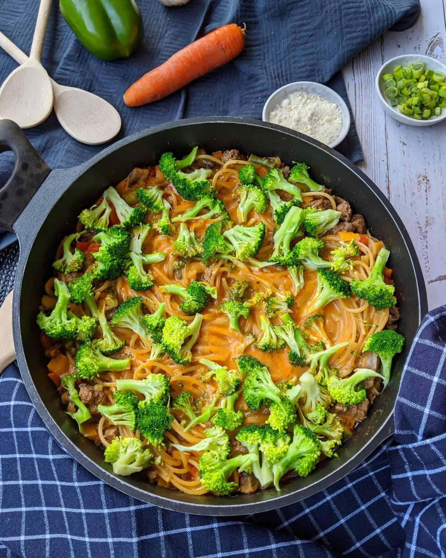 Eine Pfanne mit One pot pasta mit Brokkoli Champignons und Hackfleisch. Daneben ein Schälchen Parmesan und Gemüse als Deko.