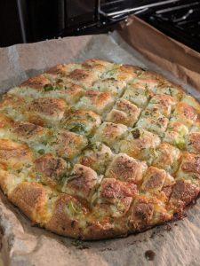 Das fertig gebackene Knoblauch-Mozzarella Brot auf einem Backblech.