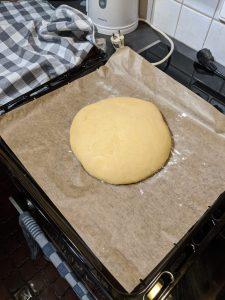 Eine Teigkugel für dass Knoblauch-Mozzarella Brot auf einem Backblech.