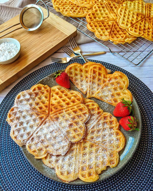Waffeln mit Erdbeeren auf einem Teller. Im Hintergrund ein Küchengitter mit Waffeln und Deko.