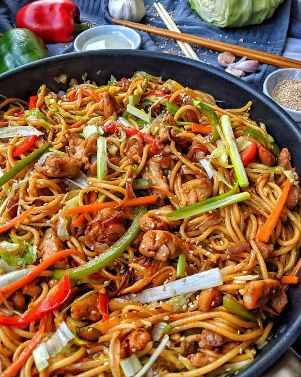 Eine Pfanne mit Hähnchen Chow Mein. Dahinter Schälchen mit Sesamkörner und Sesamöl, sowie Deko.