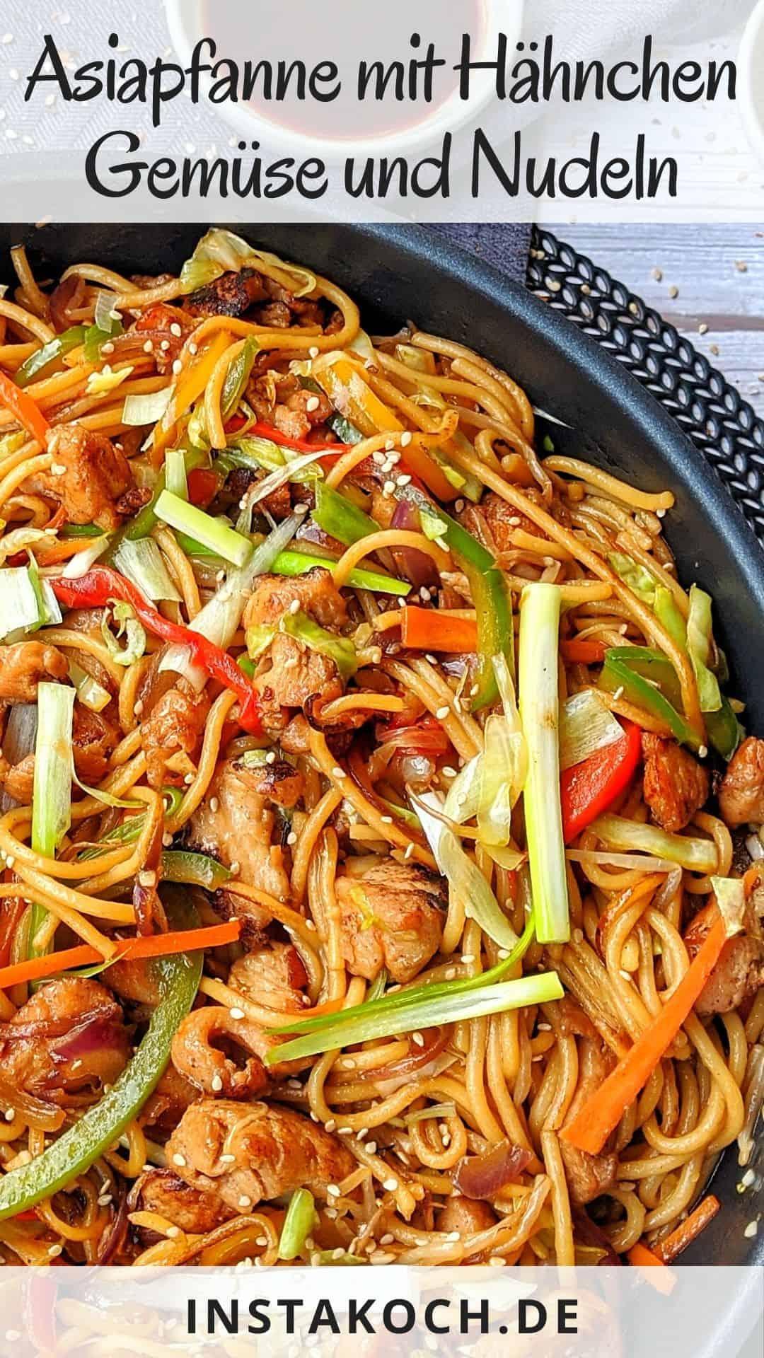 Eine Pfanne mit Hähnchen Chow Mein. Dahinter Schälchen mit Sojasoße und Sesam, sowie Deko.