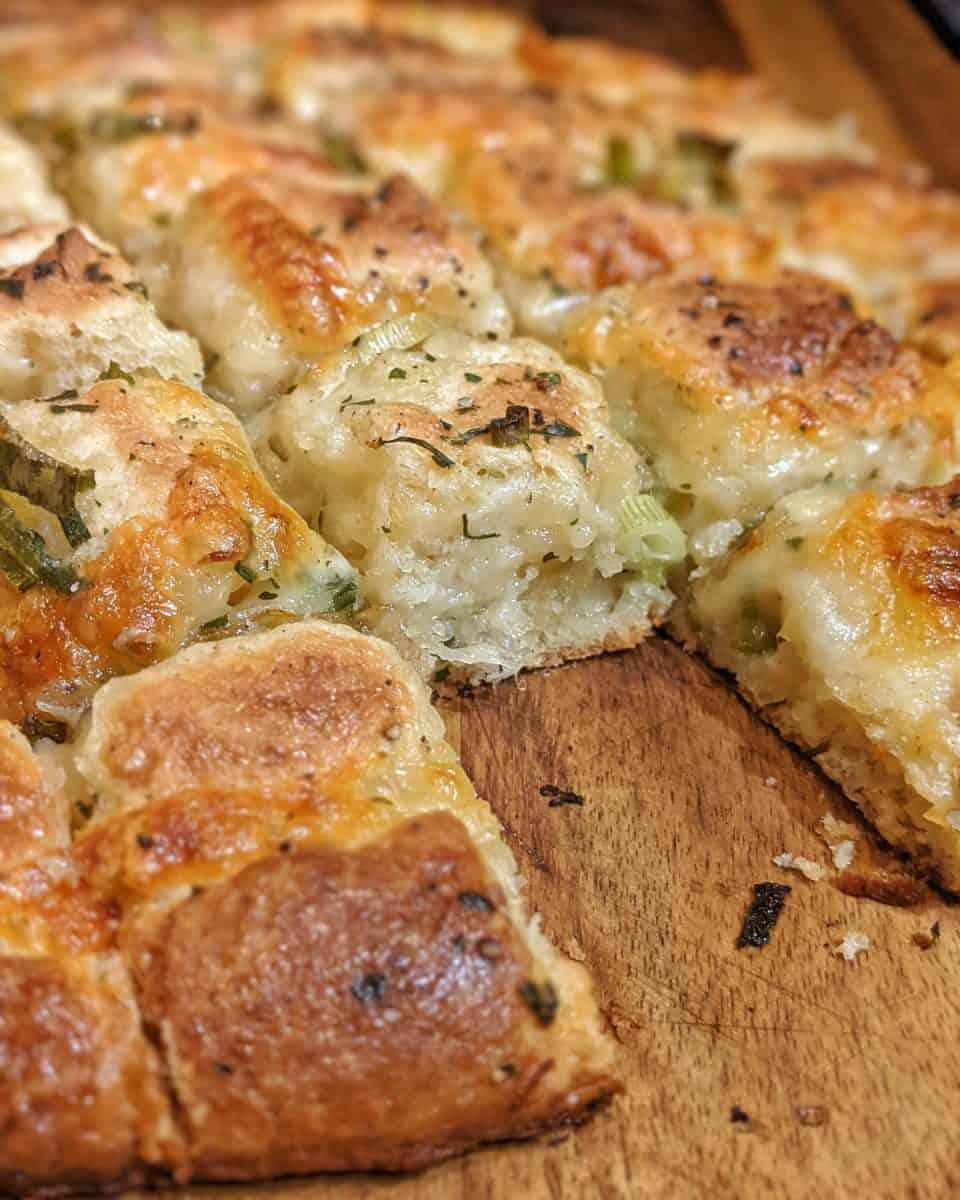 Das angeschnittene Knoblauch-Käse-Brot auf einem Holzbrett.