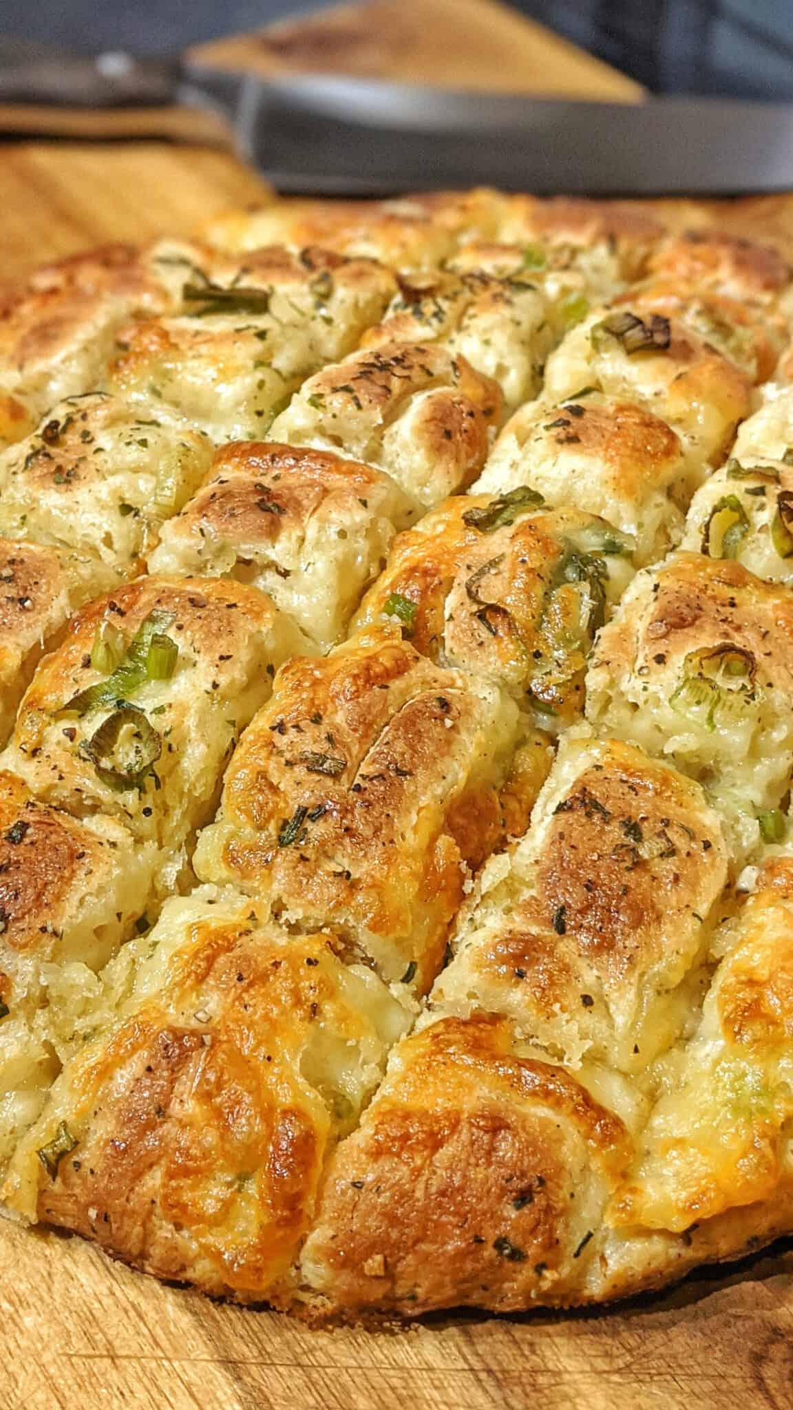 Das Knoblauch-Mozzarella Brot auf einem Holzbrett. Im Hintergrund ein Messer.