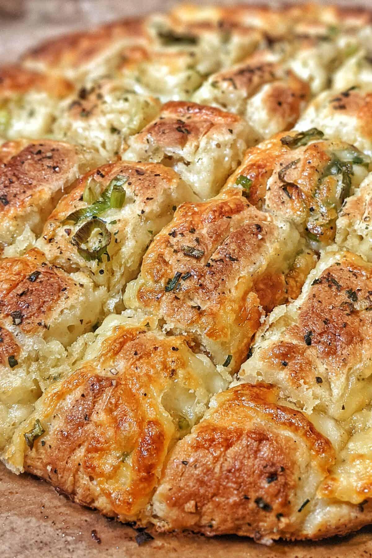 Das Knoblauch-Mozzarella Brot auf einem Holzbrett.