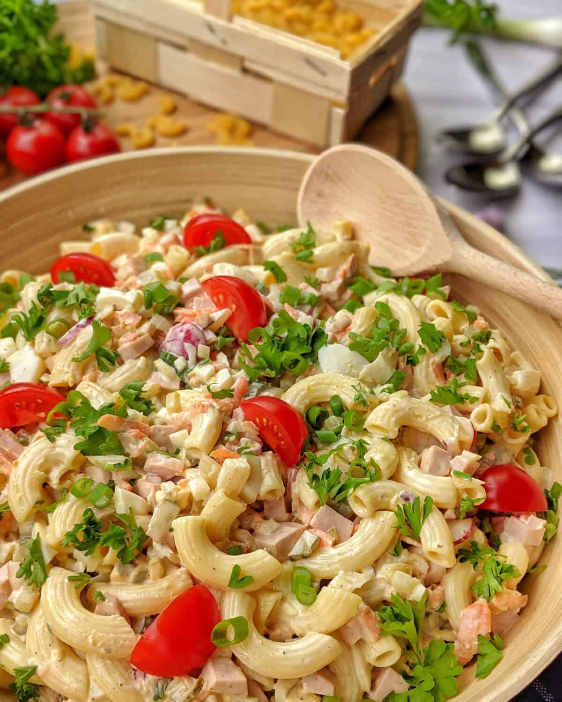 Eine Salatschüssel mit Nudelsalat. Dahinter Löffel und Krischtomanten und Nudeln als Deko.
