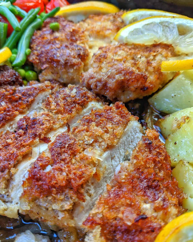 Eine Nahaufnahme von panierten Parmesan Hähnchenschnitzeln mit Gemüse und Kartoffelecken aus dem Ofen