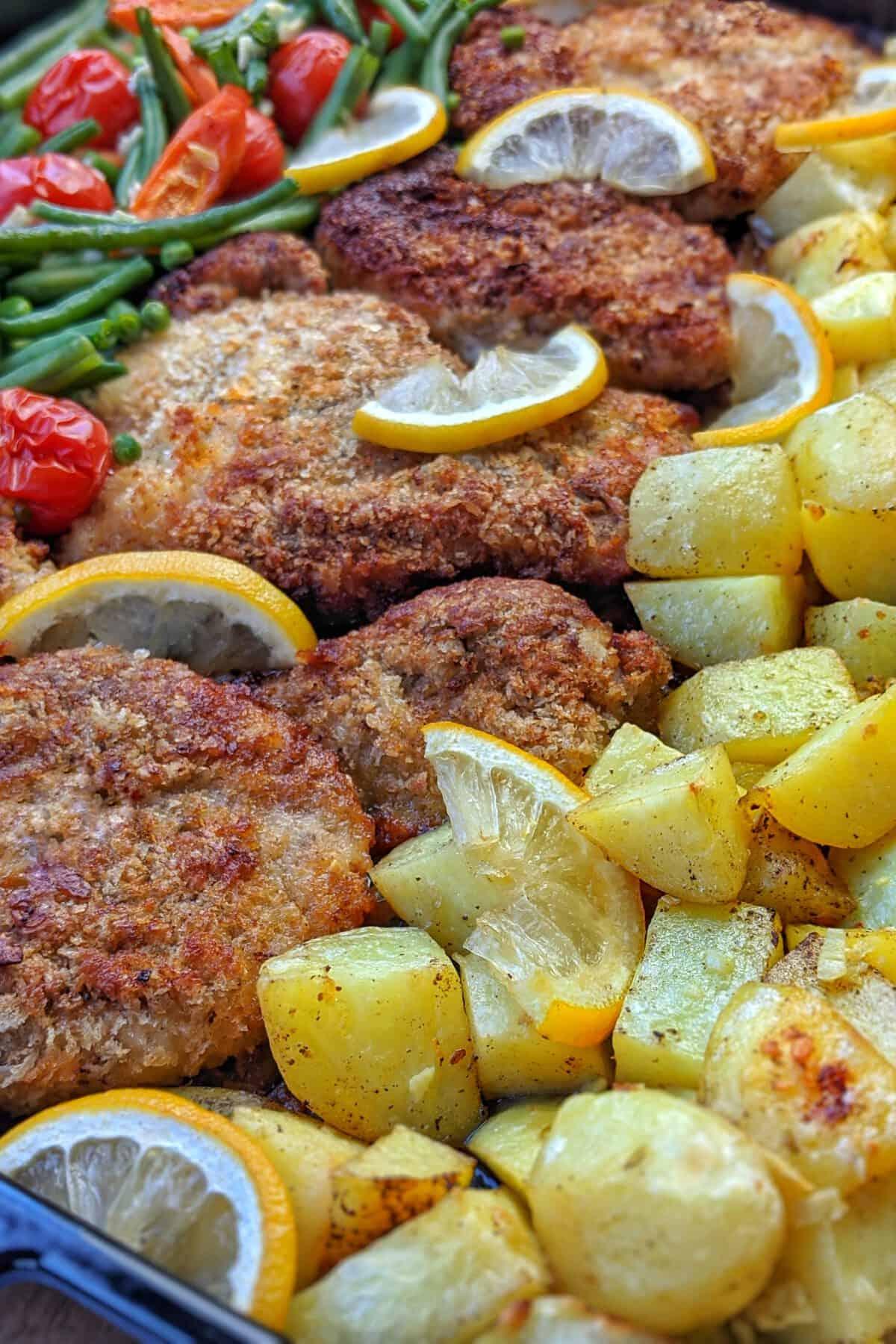 Panierte Parmesan Hähnchenschnitzeln mit Kartoffelecken und Gemüse aus dem Ofen