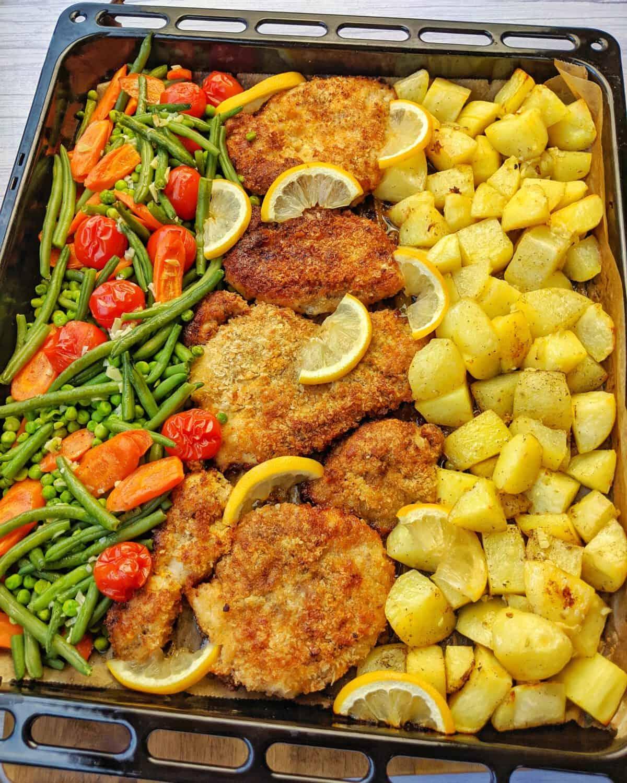 Ein Backblech mit panierten Parmesan Hähnchenschnitzeln mit Kartoffelecken und Gemüse aus dem Ofen