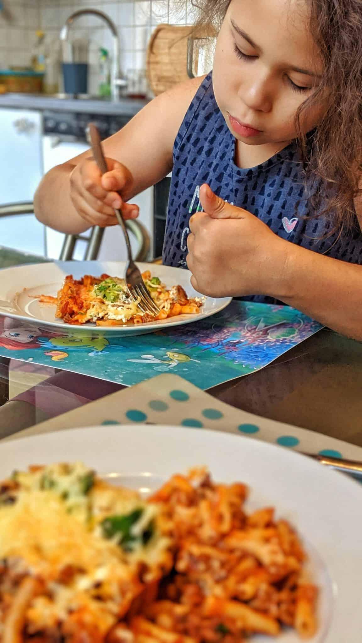 Ein Kind das Ofen-Makkaroni alla Mama isst.
