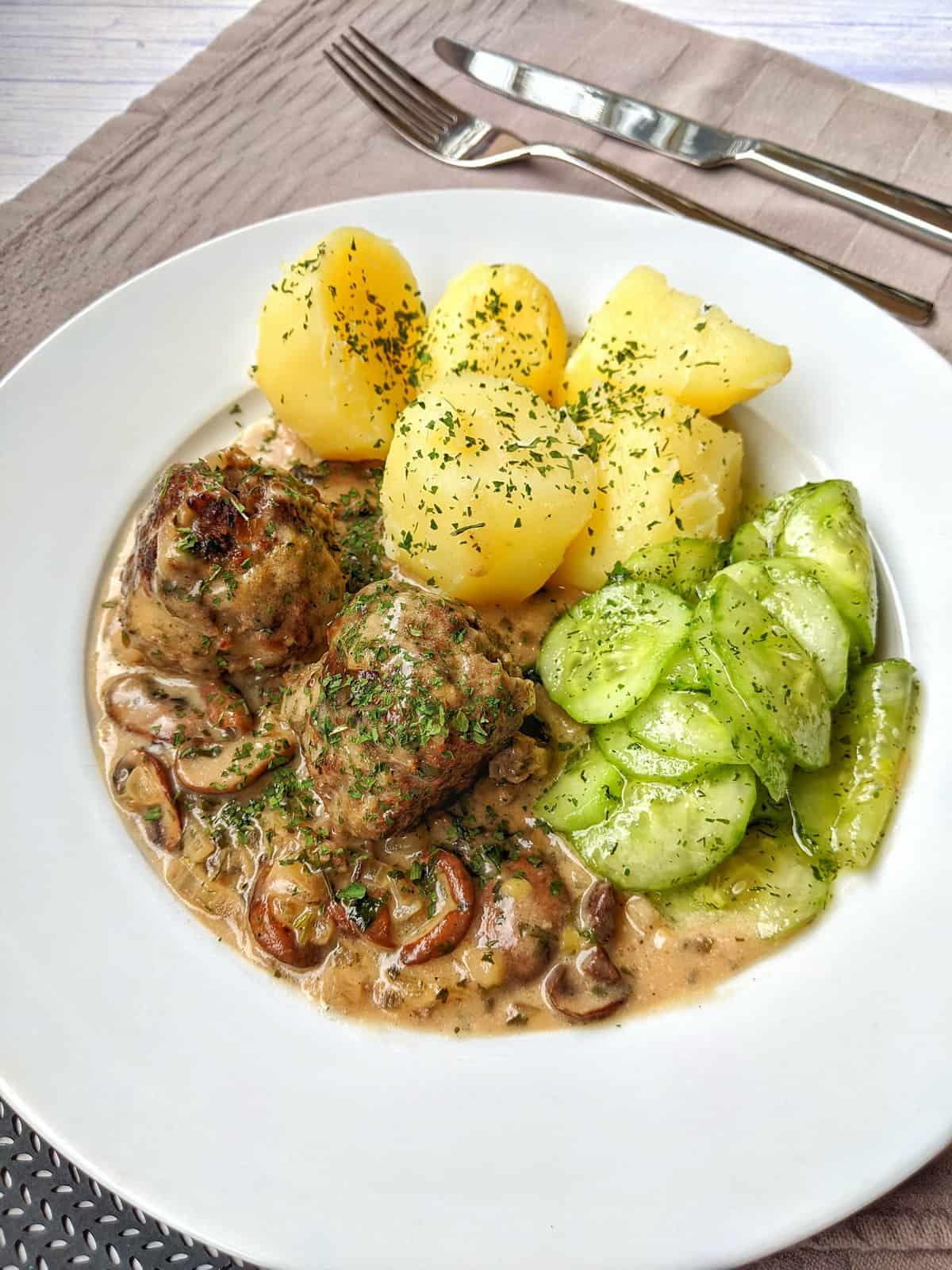 Ein weisser Teller mit Hackbällchen in Champignon-Rahmsoße, Kartoffeln und Gurkensalat.