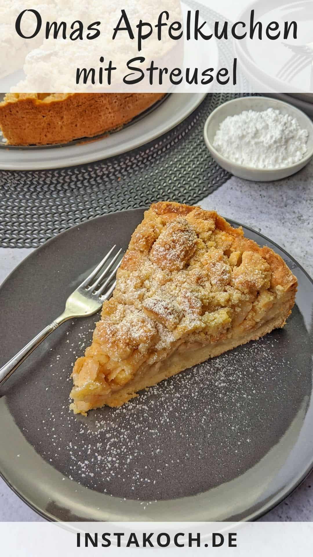 Ein Stück Apfelkuchen mit Streusel auf einem Teller. Dahinter der angeschnittene Apfelkuchen, Äpfel in einer Schale, Teller und Puderzucker als Deko.