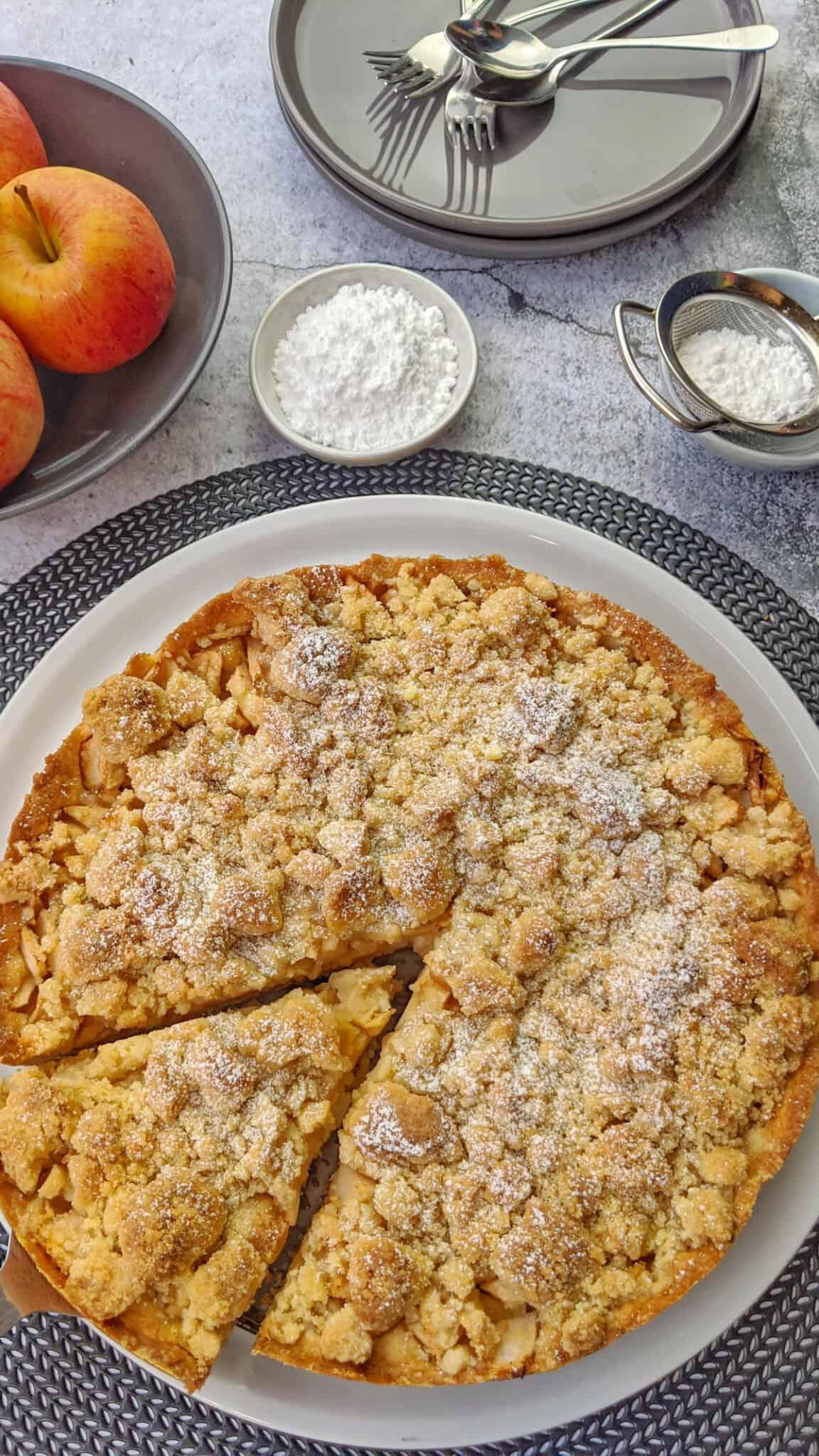 Ein Apfelkuchen mit Streusel auf einem Küchengitter. Darüber eine Schale mit Äpfeln, Teller und Puderzucker als Deko.
