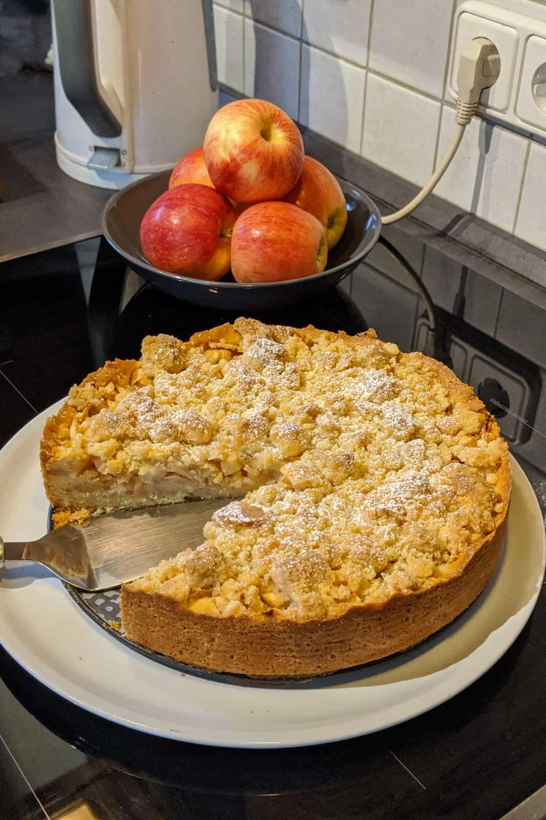 Ein Apfelkuchen mit Streusel auf einer Servierplatte. Im Hintergrund eine Schale mit Äpfeln.