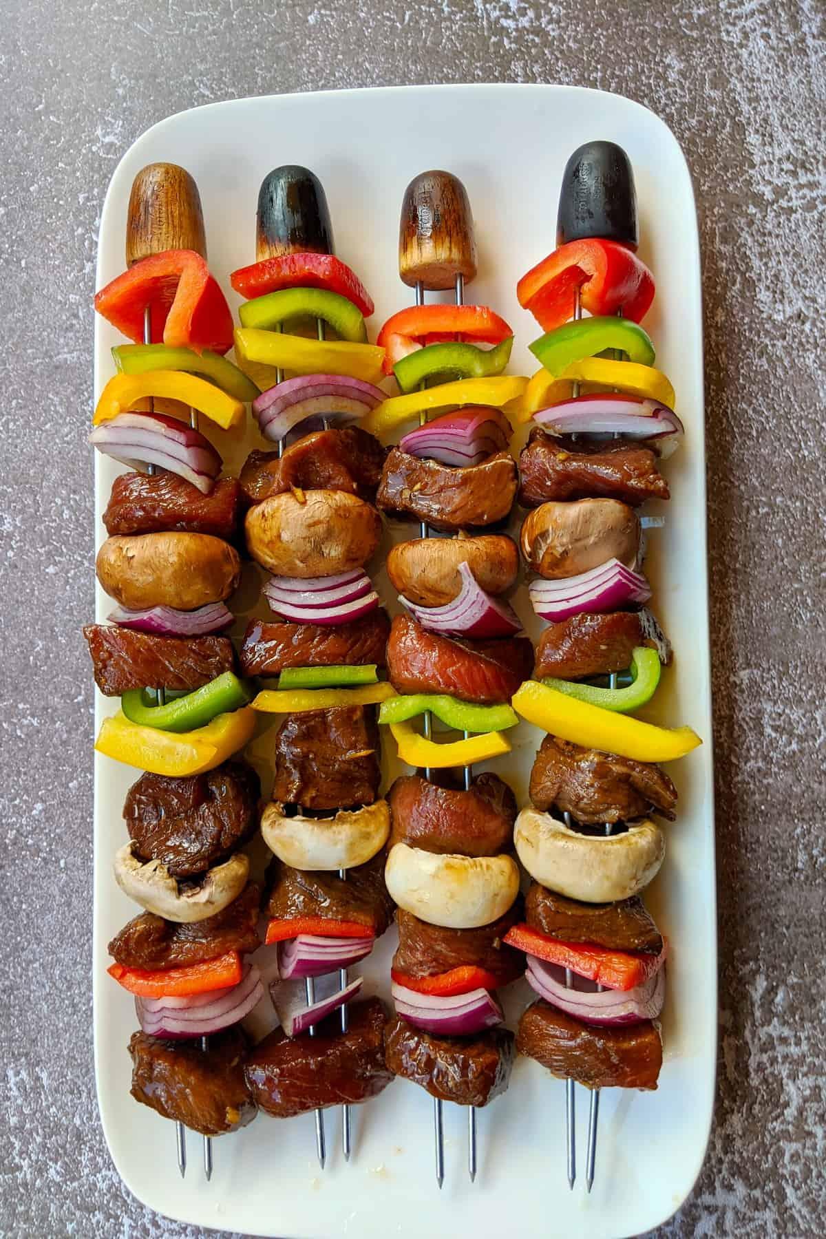 Eine weisse Servierplatte mit 4 Kebab Spiessen vor der Zubereitung.