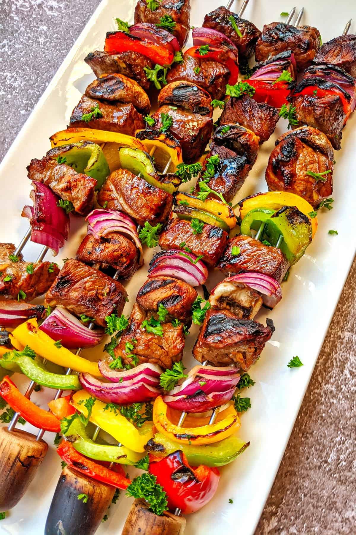 Eine weisse Servierplatte mit 4 Kebab Spiessen.