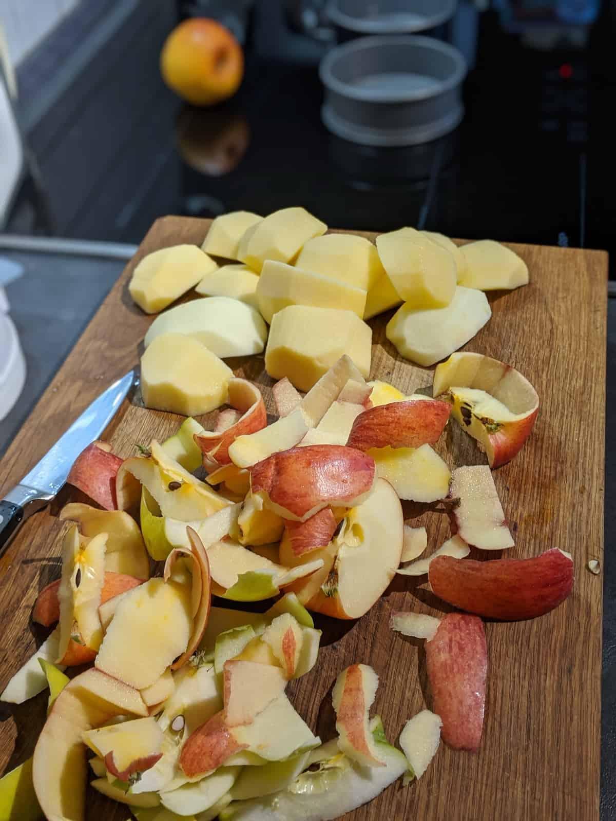 Geschälte Äpfel und Apfelschalen auf einem Scheidebrett.