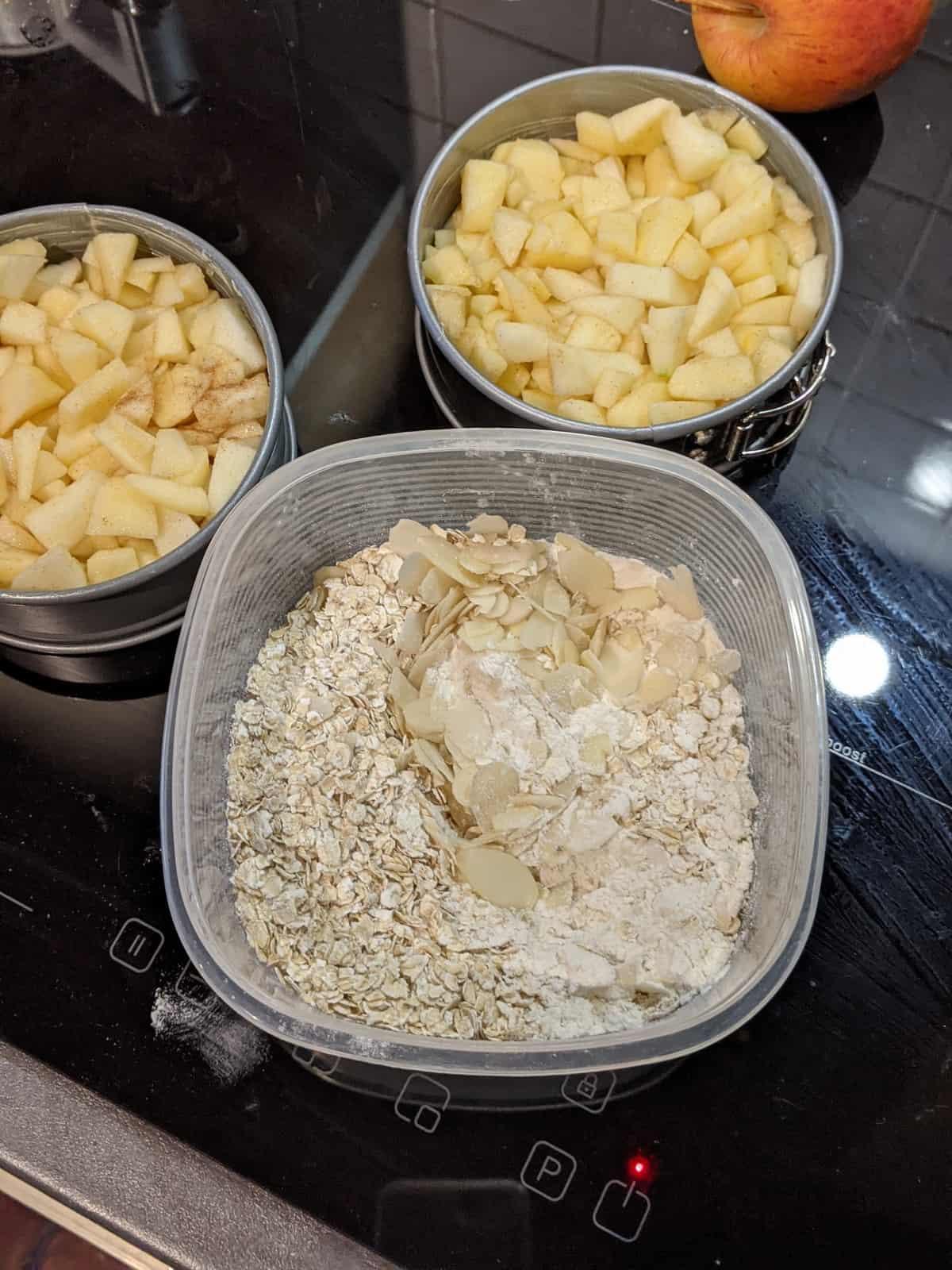 Zwei kleine Springformen mit Apfelstücken und eine Schüssel mit der Streusel-Mischung.