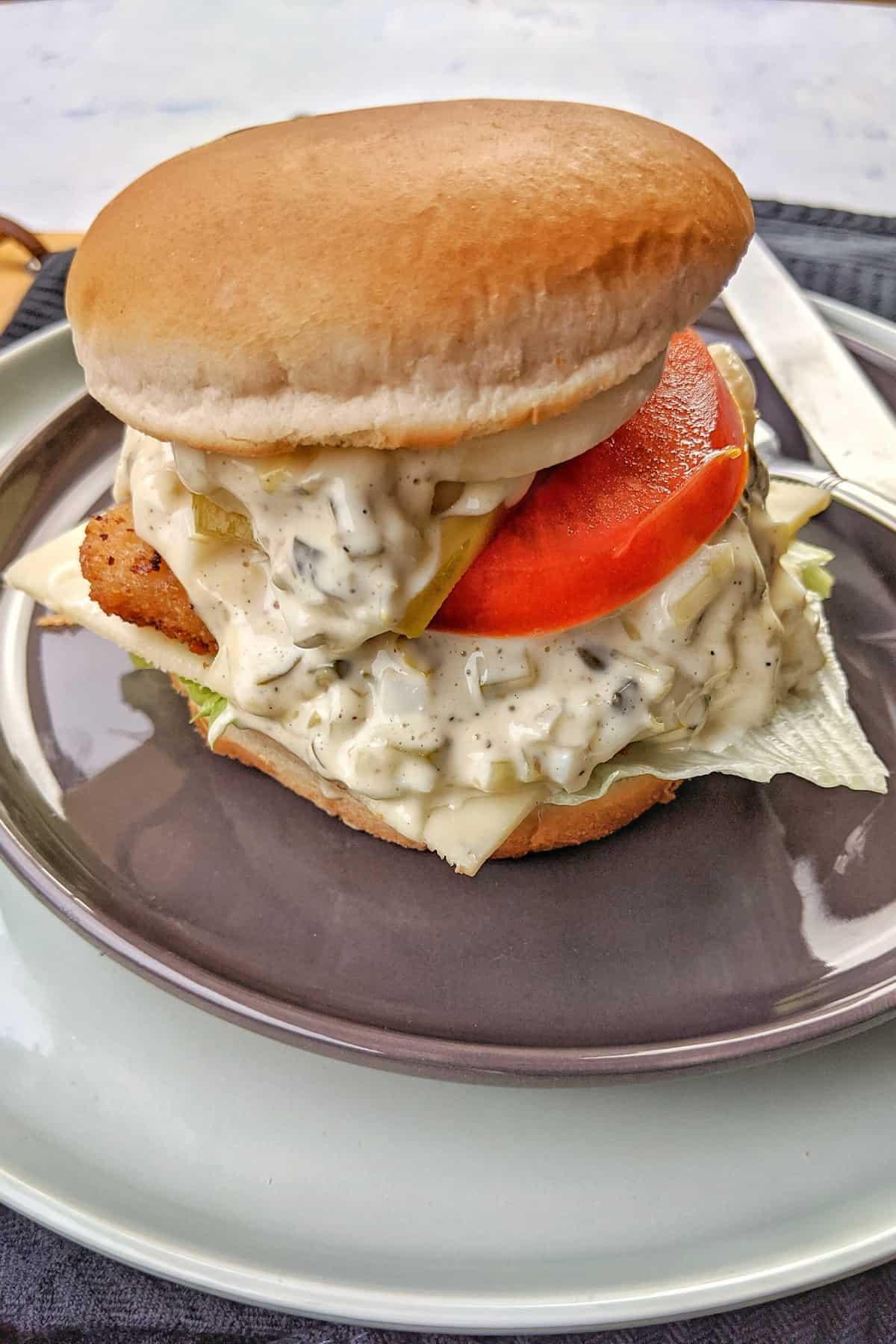 Ein Fischstäbchen Burger auf einem Teller.