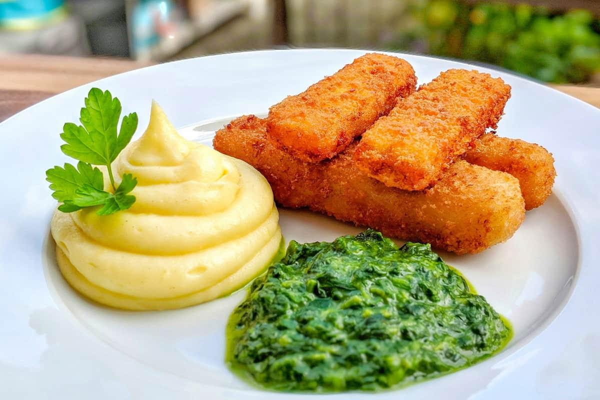 Ein Teller mit Fischstäbchen, Kartoffelpüree und Spinat.