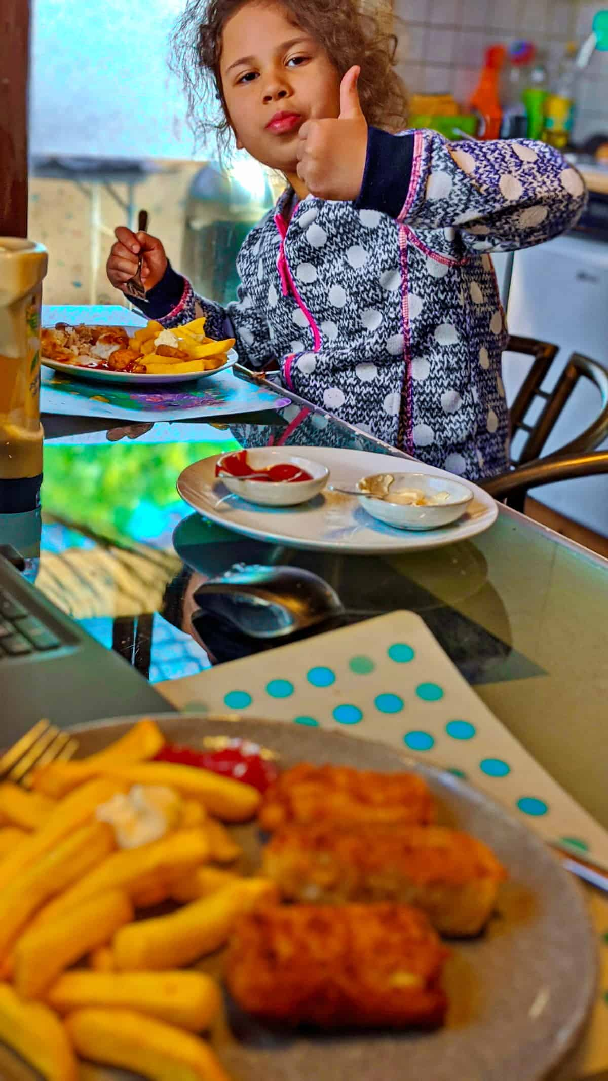 Ein Kind, das selbstgemachte Fischstäbchen mit Pommes isst. Im Vordergrund ein Teller mit selbstgemachten Fischstäbchen und Pommes.