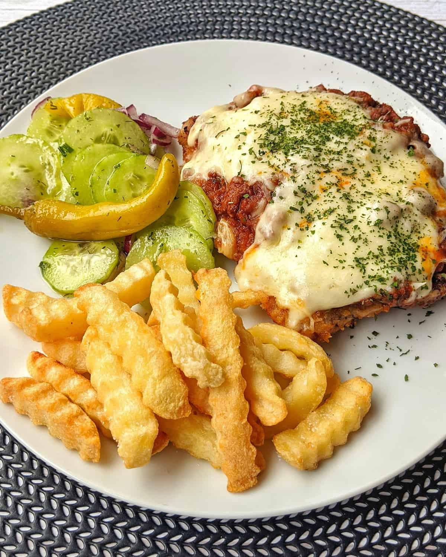 Ein Bolognese-Schnitzel mit Pommes und Salat.
