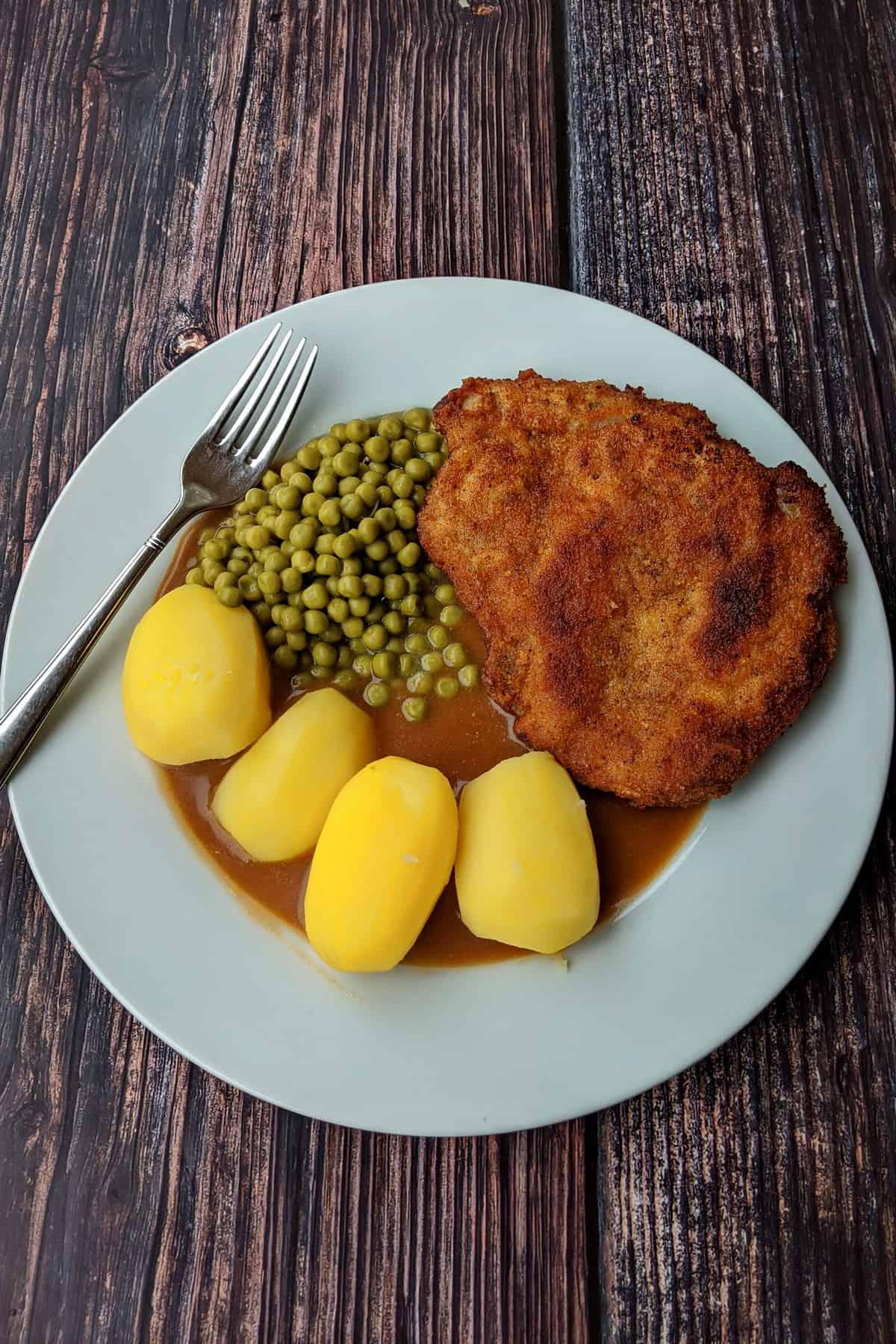 Schnitzel Wiener Art mit Salzkartoffeln, Erbsen und Bratensoße.