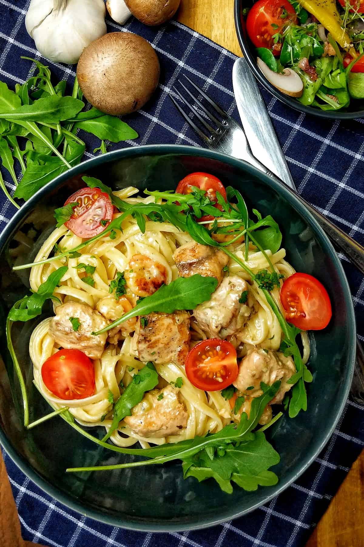 Ein dunkler Teller mit Tagliatelle mit Lachs und Scampi in Parmesan-Rahmsoße.