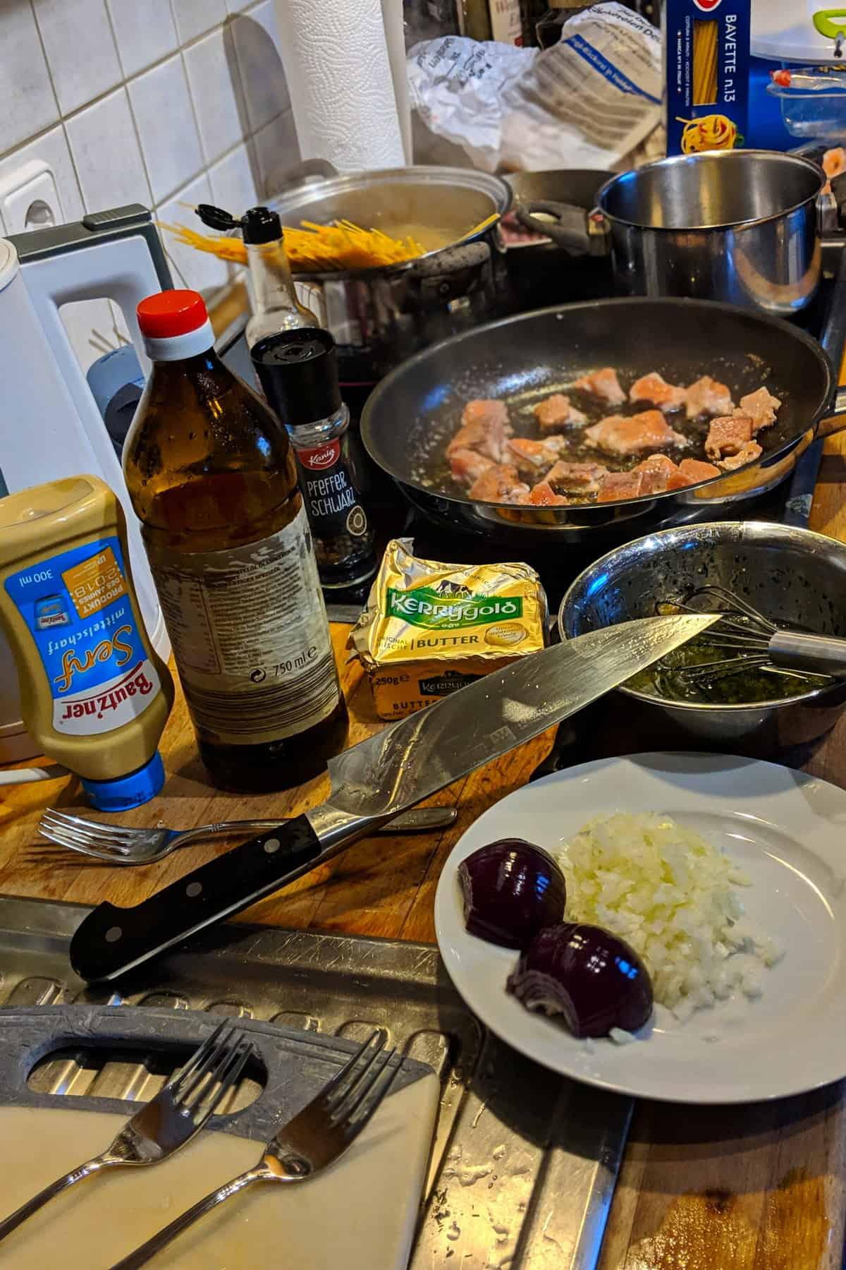 Zubereitung von Tagliatelle mit Lachs und Scampi in Parmesan-Rahmsoße in der Küche.